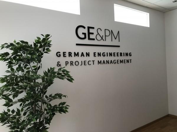 3D Acryl Logo GE&PM (8mm durchgefärbt) direkt auf die Wand geklebt