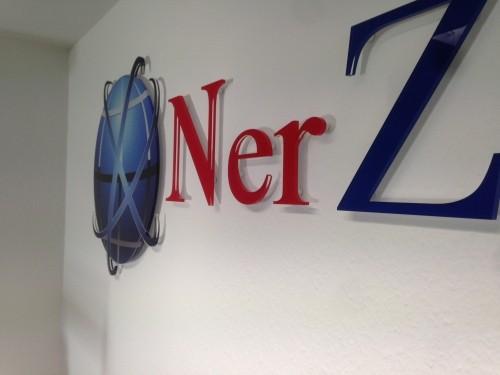 3D Acryl Logo NZ (8mm GS transparent - 4c foliert) auf Abstandshaltern montiert